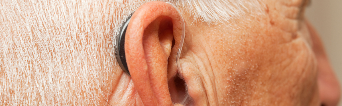 Close up of hearing aid in an older man's ear