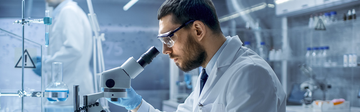 Male researcher looking into a microsope