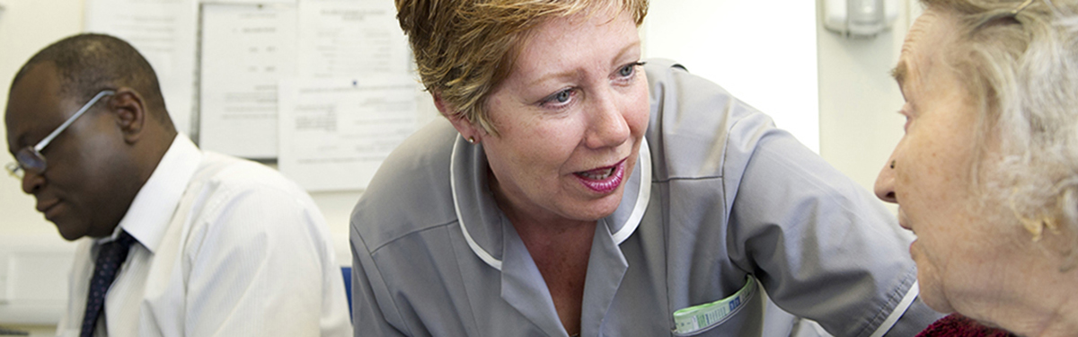 A person with dementia talking to a nurse, with a researcher in the background