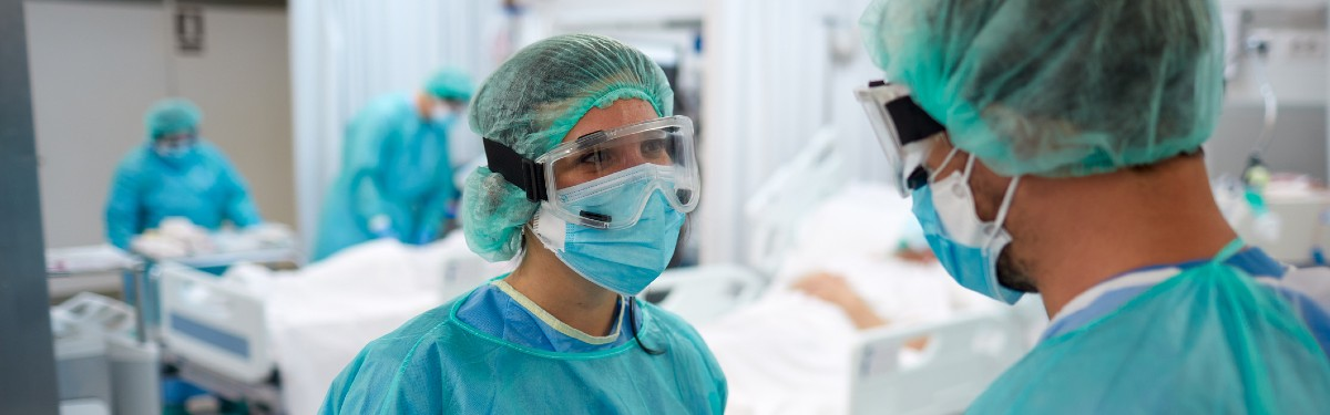 Two healthcare workers wearing personal protective equipment on a hospital ward