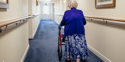 An elderly lady in a care home using a walking frame.